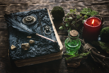 Spell book, magic potion and other various witchcraft accessories on the wizard table background.