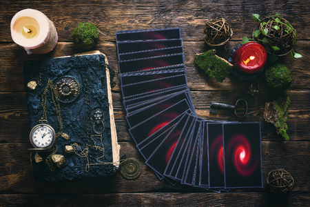 Tarot cards and book of magic on a wooden table background. Future reading.