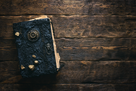 Ancient magic book on a wooden table background with copy space. Spellbook.