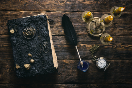 Ancient magic book, pocket watch, inkwell and a quill pen in the light of burning candle on a wooden table background. Spell book.