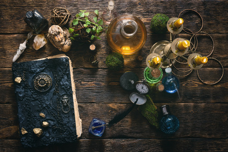 Spell book, magic potions and other various witchcraft accessories on the wizard table background. Imagens