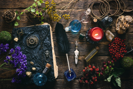 Spell book, magic potions and other various witchcraft accessories on the wizard table background. 写真素材