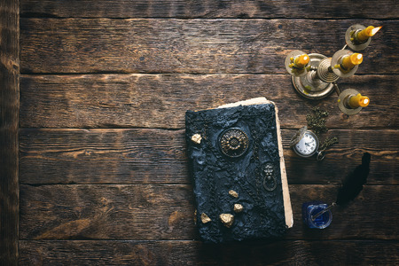 Ancient magic book, pocket watch and a black quill pen in the light of burning candle on a wooden table background with copy space. Spell book concept. 写真素材
