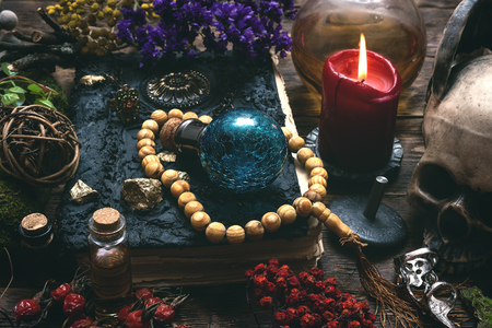 Spell book, magic potions and other various witchcraft accessories on the wizard table background. Reklamní fotografie