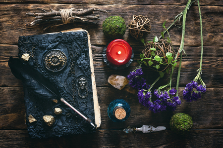 Spell book, magic potion and dryed herbs on the wizard table background.