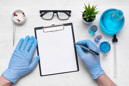 Medical examination mockup. A doctor or pharmacist is writing a notes to a blank paper sheet with a pen in his hand on laboratory table background.