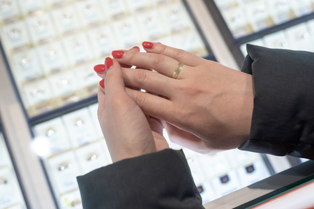 A woman is choosing a gold wedding ring in a jewelry store. 스톡 콘텐츠