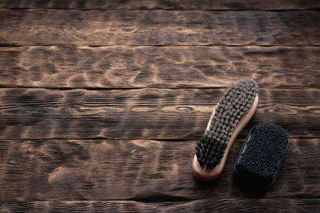 Footwear brush on a brown wooden floor background.
