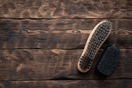 Footwear brush on a brown wooden floor background. Stock Photo