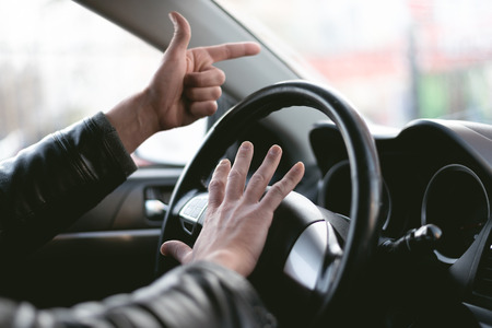 Angry driver is honking and is yelling by sitting of a steering wheel. Road aggression concept. Traffic jam. 版權商用圖片