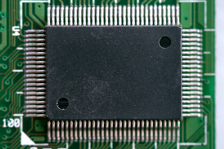 Black chip on the green circuit board abstract background.