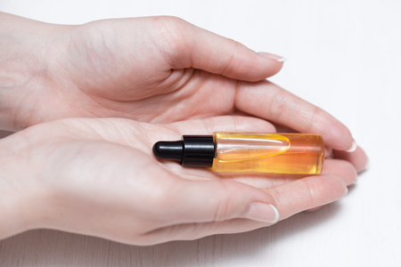 Yellow cuticle oil bottle and a female hands on a white wooden table background. Fingernail care concept.