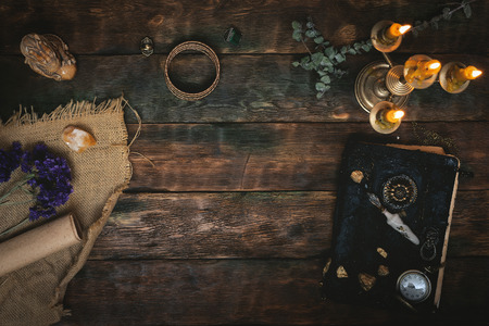 Ancient magic book and a pocket watch in the light of burning candle on a wooden table background with copy space. Spell book.