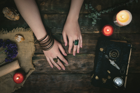 Enchantress female hands and an ancient magic book in the light of burning candle on a wooden table background with copy space. Spell book. Archivio Fotografico