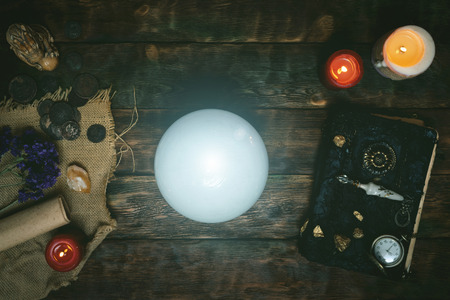 Blurred image of crystal ball and a magic book on a wizard table background. Flat lay background.