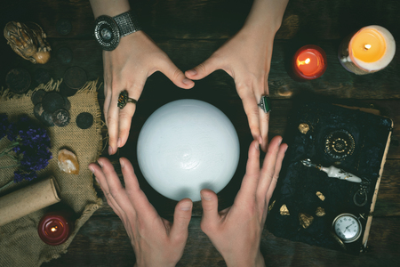 Future teller and a crystal ball is reading a future on a magic table background. Banco de Imagens