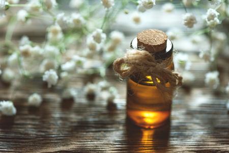 Gypsophila flower essential oil in a bottle on a wooden board background. Herbal medicine. 写真素材
