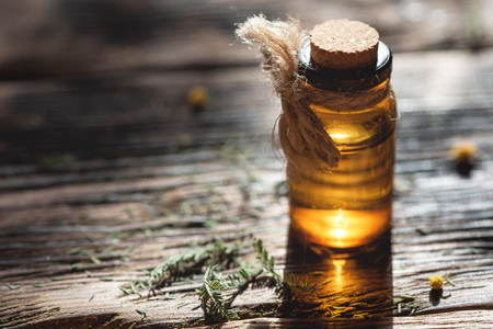 Essential oil in a brown transparent bottle on a wooden board background. Herbal medicine.