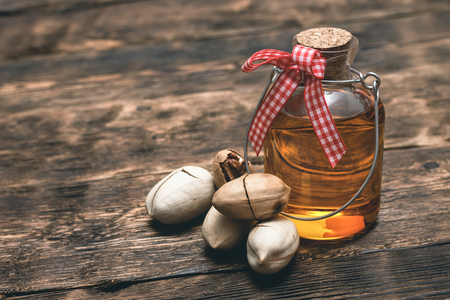 Pecan nut oil in a bottle on brown wooden table background.