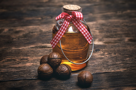 Macadamia oil in the bottle on the wooden table background. Banco de Imagens