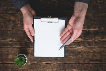 Signing of business contract or agreement mock up. To do list with copy space. Blank paper page in a businessman hands on office table background.