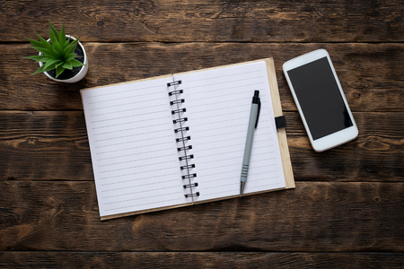 Notebook with a blank pages and a mobile phone with blank screen on an office table background. Contact us.