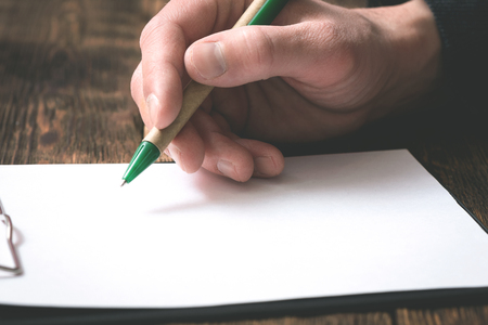 Businessman is signing a blank document on office table by a pen in his hand.