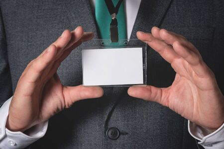 Blank name badge with a copy space in a businessman hands. Stock Photo