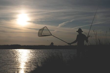 Fisherman silhouette with a rod on the pond.