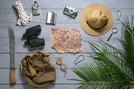 Treasure map and other travel accessories on a wooden floor flat lay background. Adventure concept.