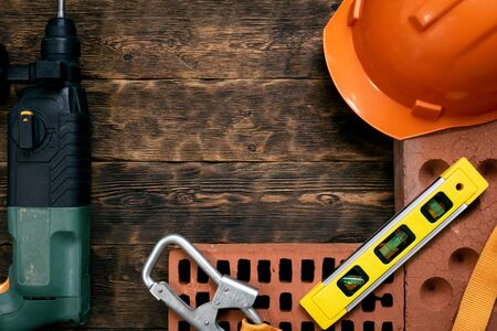 Construction concept background with a copy space. Hardhat, brick, hammer drill and a bubble level on a brown wooden workench.