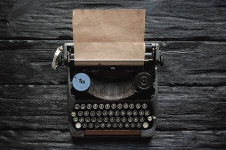 Old typewriter on a writer black wooden desk flat lay background with copy space.