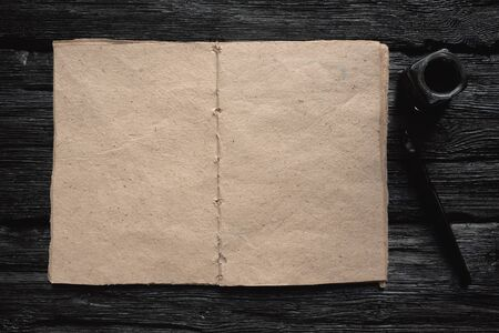 Blank page book with a copy space and a quill pen on a black wooden table flat lay background.