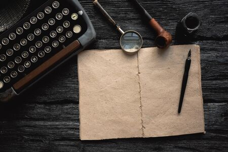 Blank page book with a copy space and old typewriter with letter on a black wooden table flat lay background with a copy space.