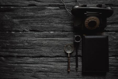 Black old rotary phone, quill pen, magnifying glass and book on a black wooden table flat lay background with copy space. Contact us.