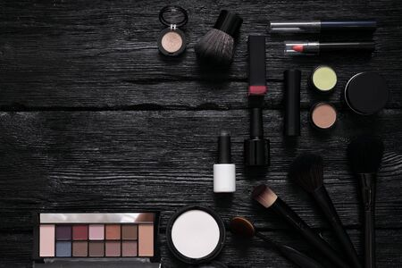 Makeup brushes and cosmetics flat lay background with a copy space. Make up accessories on a black wooden table.