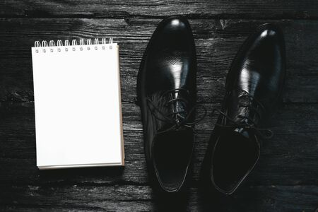 Businessman black shoes and a blank page notepad on black background.