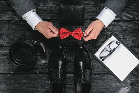 Business flat lay background. Male shoes, wallet,contract, belt and a businessman hands with a red bow on black wooden table background.