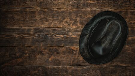 Old black leather hat on a brown wooden table flat lay background with a copy space.