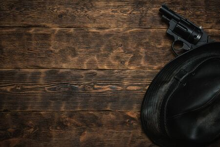 Black leather hat and gun on a wooden table of detective agent flat lay background with copy space.