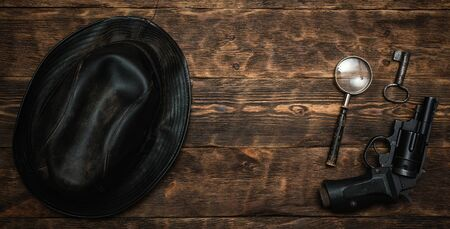 Detective or spy agent wooden table flat lay background with copy space. Handgun, black leather hat, magnifying glass and a rusty key on the work table.
