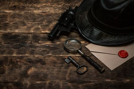 Top secret envelope, gun, leather hat, key and magnifying glass on a wooden table of detective agent table background.