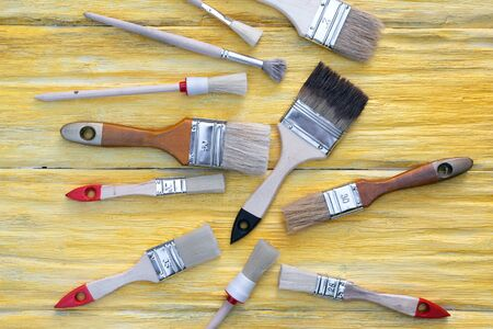 Paint brushes collection on a yellow wooden board flat lay background.