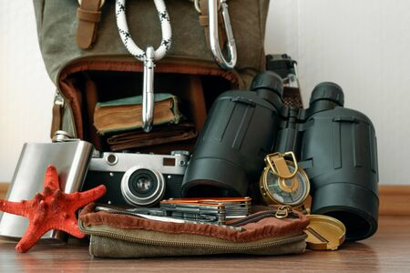 Travel or adventure background. A backpack with a safety rope with carabines, binoculars, compass, hip flask, book and photo camera on a floor on a white wall background.