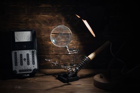 Retro analog voltmeter and soldering iron in the light of lamp on a brown wooden table background. Electrical works abstract background.