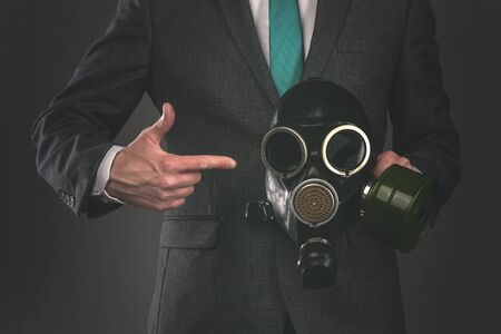 Man is showing on a gas mask in his hand on a gray background. Pollution of environment concept. Air pollution.