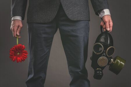 Man is holding in hands a red gerbera flower and gas mask on a gray background. Pollution of environment concept.