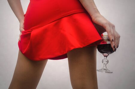 Girl is holding a glass of wine at the level of the sexy thighs in pantyhose. Romantic date. Standard-Bild