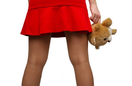 Sexy female hips in in stockings and in short red dress and hand with toy isolated.