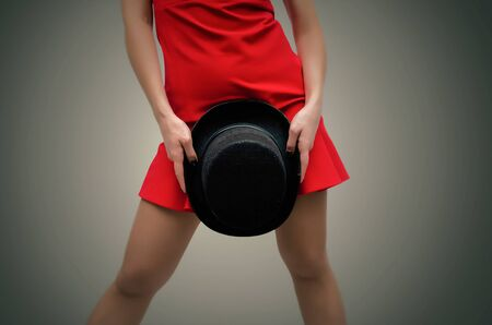 Woman in red dress and stockings is holding in hands a black bowler hat in front of herself isolated on dark background.